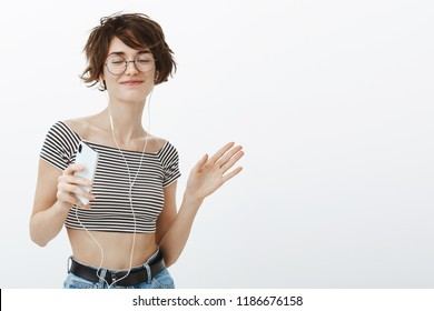 Oh yeah, favorite song makes me dance. Happy relaxed attractive girlfriend with short brown hair in glasses and cropped top, enjoying music in earphones, holding smarpthone with closed eyes and smile