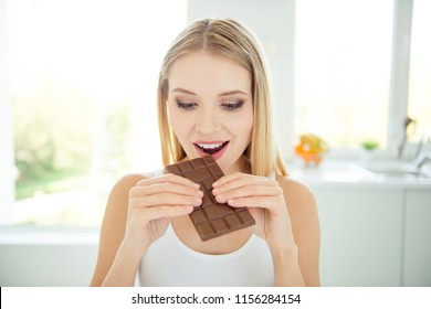 Oh yummy temptation concept! Close up photo portrait of excited joyful funny funky cheerful satisfied lady licking chocolate bar in hands sitting in light modern room