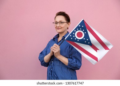Ohio flag. Woman holding Ohio state flag. Nice portrait of middle aged lady 40 50 years old holding a large state flag over pink wall background on the street outdoor.