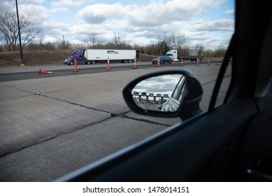 Ohio Turnpike 80, USA/ March 22 2019: Indiana Ohio Turnpike booths in rear view mirror of car.