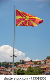 OHRID, MACEDONIA - CIRCA JUNE 2017 - The bright red and yellow flag of Macedonia flies proudly in Ohrid, Macedonia.  In the background, Tsar Samuel's Fortress sits on a hilltop