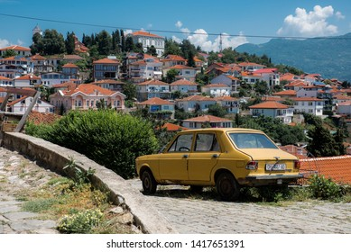 Ohrid, North Macedonia - 06.05.2018: Houses located on a hill and a yellow zastava (a yugoslav car) in the city of Ohrid, North Macedonia on a sunny summer day
