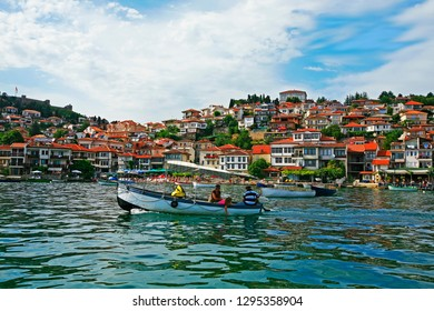 Ohrid, Republic of North Macedonia (ex-FYROM) / 08 20 2014 : Small tourist boat with passengers on the lake of Ohrid, in front of houses of city of Ohrid, Republic of North Macedonia