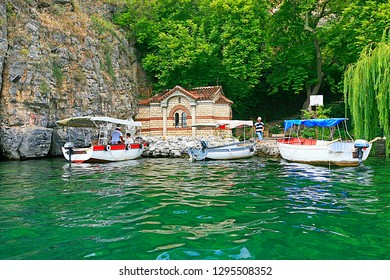 Ohrid, Republic of North Macedonia (ex-FYROM) / 08  18 2014 : Docked little boats in front of the tiny church of Nativity of the Holy Mary on the lake of Ohrid, North Macedonia, Central Europe