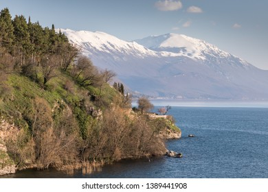 Ohrid/North Macedonia - March 28,2018: A view of the snowcapped mountains surrounding Lake Ohrid with a green headland in the foreground.