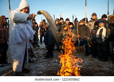 Oi Village, Khangalassky Ulus, Republic of Sakha (Yakutia)/Russia - October 31 2014: the shaman conducting traditional feeding of fire spirits before ice fishing for crucians