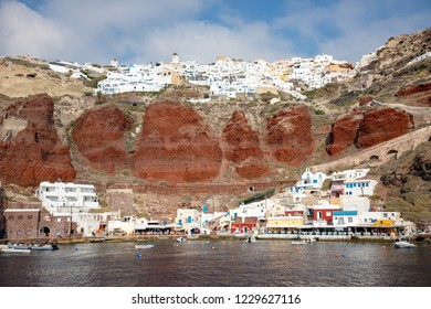Oia, Greece - 18.11.2018: View of Oia village with white houses on red rocks caldera of Santorini Island in Greece