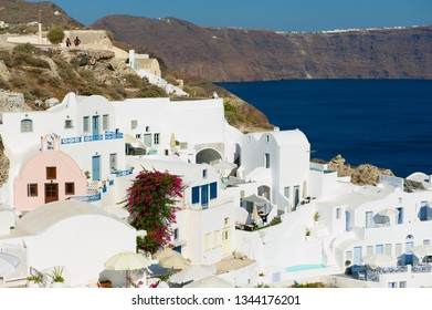 Oia, Greece - August 02, 2012: Hotel buildings at the cliff with a sea view to volcanic caldera in Oia, Greece.