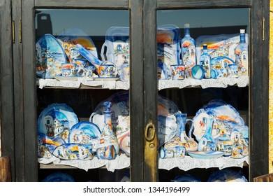 Oia, Greece - August 02, 2012: Traditional handmade souvenirs from Santorini island at the shelf of a street souvenir shop in Oia, Greece.