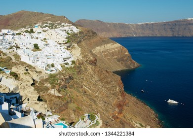 Oia, Greece - August 02, 2012: Traditional white painted  buildings at the cliff with a stunning sea view to the volcanic caldera in Oia, Greece.