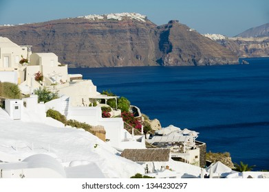 Oia, Greece - August 02, 2012: Hotel buildings at the cliff with a stunning sea view to volcanic caldera in Oia, Greece.