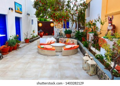 Oia, Santorini - April 25, 2019: Oia, cafe in Santorini island, Greece with traditional decorations, donkeys and sofa chairs