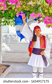 Oia, Santorini - August 24, 2018:  Greek man in Traditional National Costume Greets Visitors Against National Greek Flag in Oya Village in Santorini in August 24, 2018
