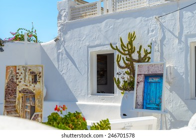 OIA, SANTORINI, GREECE - AUGUST 12, 2013: Wall decoration with pictures and cactus in Oia town on August 12, 2013