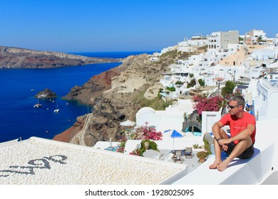Oia, Santorini, Greece - July 22, 2016: Man seating on wall at a luxury hotel. In background, great view of the caldera, sea and typical cliff houses with terraces.