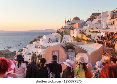Oia, Santorini, Greece - Oct 10, 2017: Crowds of international tourists watching and taking travel photos of sunset on Santorini island on 11th of October, 2017 on Santorini, Greece.