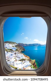Oia town on Santorini island, Greece. Traditional and famous houses and churches with blue domes over the Caldera, Aegean sea through a frame of plane window.