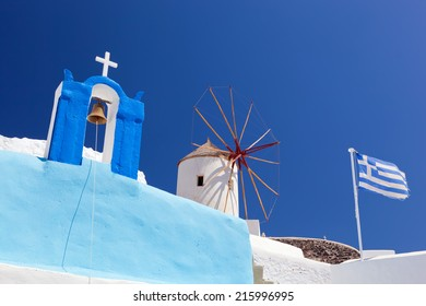 Oia town on Santorini island, Greece. Famous windmills, church and flag on cliff over the Caldera, Aegean sea.