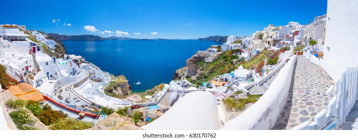 Oia town on Santorini island, Greece. Traditional and famous houses and churches with blue domes over the Caldera, Aegean sea, panorama