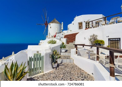 Oia town, Santorini island, Greece. Famous windmills on cliff, cobled streets and white houses over the Caldera, Aegean sea.