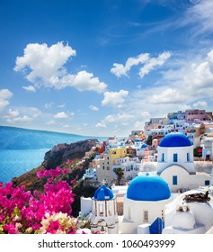 Oia, traditional greek village of Santorini with blue domes of churches under sky with flowers, Greece