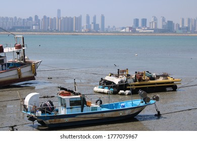 Oido, Korea-July 15, 2020: Industrial fishing boats on a low tide seabed facing the Oido city skyline