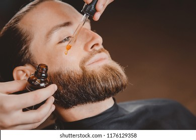 Oil for beard in dropper, process of moisturizing hair.