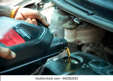 oil being poured during an oil change to a car