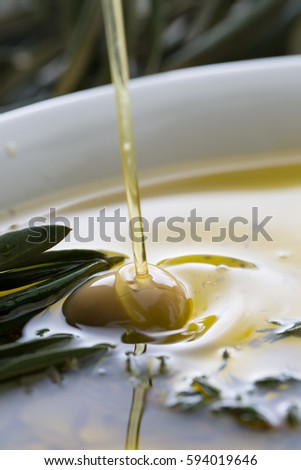 bc7ba7c0d737 Oil being poured onto an olive in white plate filled with olive oil. Close  up