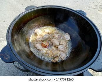 Oil boils in a cast-iron cauldron. Frying meat in hot sunflower oil. Deep-Fried.