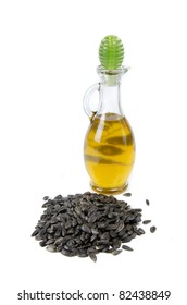 oil in bottle and sunflower seeds on white background
