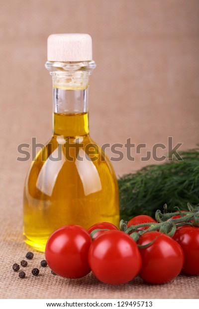 oil  in a bottle with tomato on sacking background