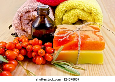 Oil in a bottle, two homemade soap, towels, twig and berries of sea buckthorn on a wooden board