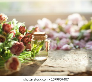 Oil bottle. Wooden table. Red flowers. Perfumes. Aroma. Flowering. Red flowers. Wooden tale. Blur background.