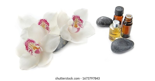 oil bottles and pebbles with beautiful orchids  on white background