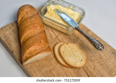 Oil and bread on a wooden board. Knife for butter and pieces of a loaf on the board.