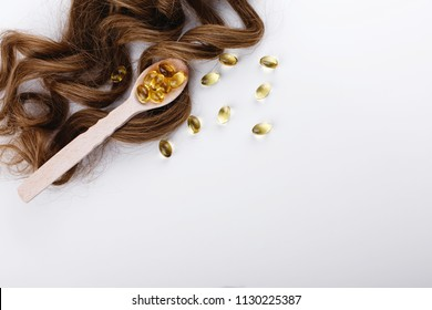 Oil capsule for hair with vitamin E lie on wooden spoon on brown hair curls
