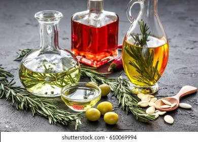 oil in carafe with spices, olives and chili on stone background