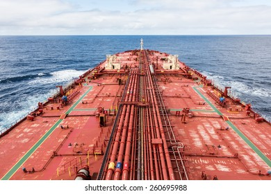 Oil carrier red deck with pipes, under cloudy sky, soft lighted. - stock photo