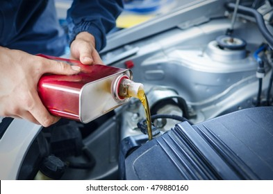 Oil change and car service. Mechanic is changing the oil of the car. Act of pouring..