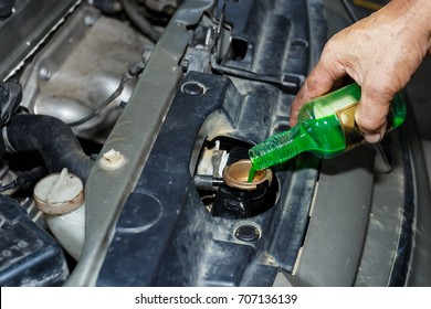 Oil change,Pouring oil to car engine, car mechanic changing motor oil in automobile engine at maintenance repair service station in a car workshop,Coolant.