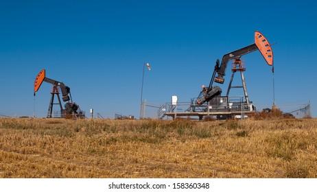 Oil dereks in a wheat field in Alberta, Canada.