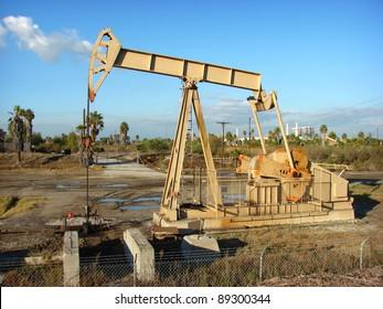oil derrick in field with blue sky
