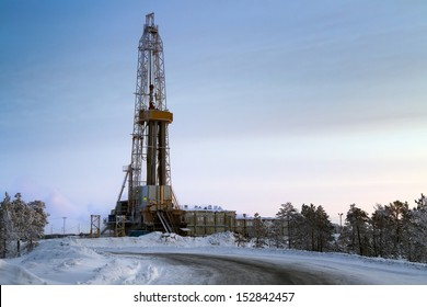 Oil derrick and the leader to it road  in the winter in twilight in Western Siberia, Russia