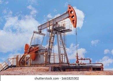 oil  derrick pumps oil into a well against a blue sky background