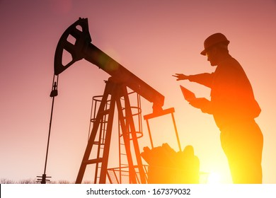 Oil Drill, field pump jack silhouette with setting sun and worker.Refinery, natural gas. Lens Flare. See more images and video from this series