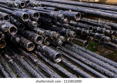 Oil Drill pipe. Rusty drill pipes were drilled in the well section. Downhole drilling rig. Laying the pipe on the deck. oil well production line with rod pump surface facility
