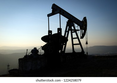 Oil drill silhouette over the village on blue evening sky