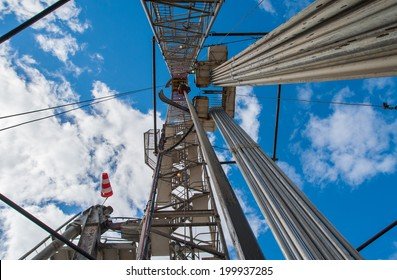 Oil drilling rig against a blue sky with clouds