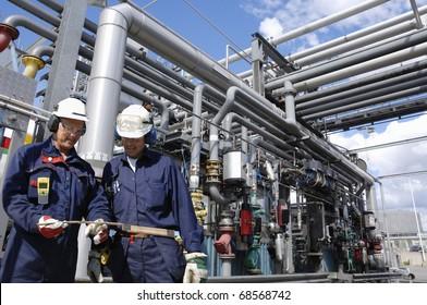 Ölingenieur, Mitarbeiter vor großen Rohrleitungen und Brennstoffbau in der Raffinerie